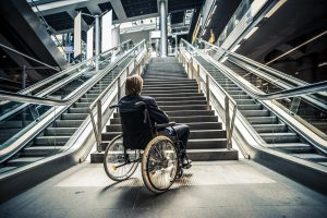 Person in a wheelchair at the bottom of a flight of stairs.