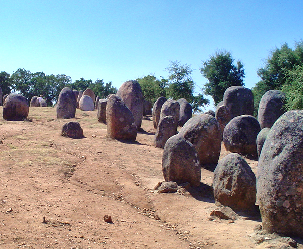 Photo of a row of standing stones at the Cromeleque dos Almendres (Évora, Portugal), a megalithic stone setting in Iberia.