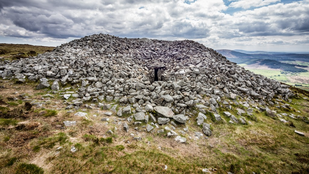 Photo of Neolithic passage tomb on the summit of Seefin Mountain, County Wicklow, Ireland. The tomb is covered by a huge circular cairn which is 24 metres in diameter, 3 metres in height and has a kerb of large boulders. A narrow passage, 11 meters in length, opens into a rectangular chamber, in which there are five recesses.