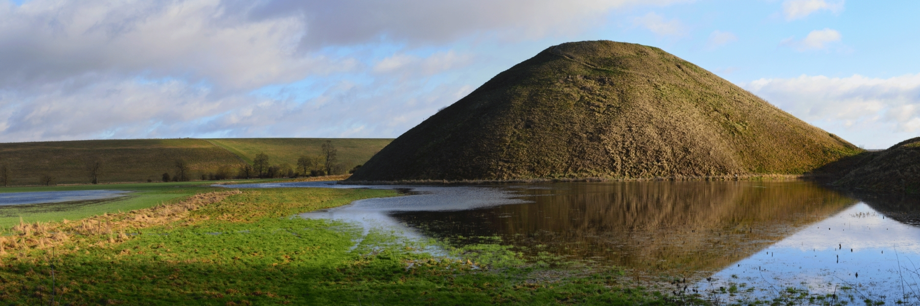 Photo of Silbury Hill Neolithic mound. It stands 30 metres high and 160 metres wide, and comprises half a million tonnes of chalk. It is a huge non-megalithic accomplishment.